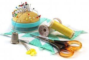 Sewing stuff - pincusion, thimble, thread, scissors, quilting square, and quilting pins, isolated on white.